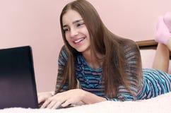 Mulher de sorriso bonita nova que usa o laptop que encontra-se na cama Fotografia de Stock