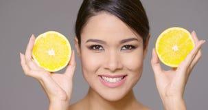 Mulher de sorriso bonita que guarda metades do limão video estoque