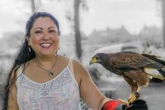 Mulher de sorriso bonita que levanta com um falcão da águia em sua mão imagem de stock royalty free