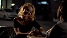 Mulher de sorriso bonita que senta-se com o amado no terra?o do caf?, data perfeita, amor imagem de stock
