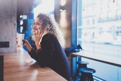 Mulher de sorriso bonita que senta-se no café urbano e que fala com os amigos através do smartphone móvel Retrato ocasional de co foto de stock royalty free