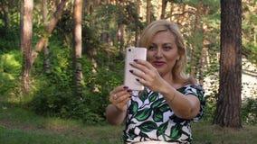 Mulher de sorriso bonita que tem o bate-papo video com o telefone no parque filme