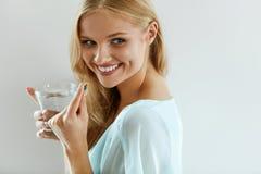 Mulher de sorriso bonita que toma o comprimido da vitamina Suplemento dietético fotografia de stock royalty free