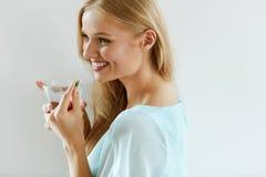 Mulher de sorriso bonita que toma o comprimido da vitamina Suplemento dietético imagens de stock