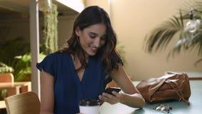Mulher de sorriso bonita que usa o telefone esperto video estoque