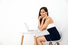 A mulher de sorriso caucasiano bonita que fala no telefone ao usar o portátil na mesa branca sobre o branco isolou o fundo imagens de stock