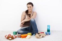 Mulher de sorriso cercada por brinquedos do bebê fotografia de stock