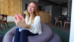 A mulher de sorriso chama Skype na pilha através do Internet, sentando-se na cadeira macia no caf moderno no dia do outono filme