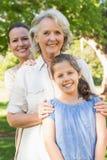 Mulher de sorriso com avó e neta no parque fotos de stock