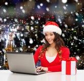 Mulher de sorriso com caixa de presente e portátil Fotografia de Stock Royalty Free