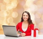 Mulher de sorriso com cartão e portátil de crédito Foto de Stock