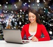Mulher de sorriso com cartão e portátil de crédito Fotografia de Stock Royalty Free