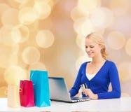 Mulher de sorriso com cartão e portátil de crédito Fotografia de Stock