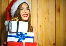 A mulher de sorriso com chapéu de Santa mantém a caixa de presente contra o backg de madeira imagem de stock royalty free