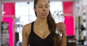 A mulher de sorriso com corpo do ajuste bebe a água no gym da aptidão filme
