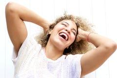 A mulher de sorriso com dirige para trás e as mãos no cabelo Fotografia de Stock