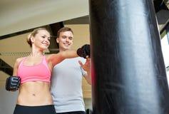 Mulher de sorriso com encaixotamento pessoal do instrutor no gym Imagem de Stock