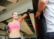 Mulher de sorriso com encaixotamento pessoal do instrutor no gym Fotografia de Stock Royalty Free