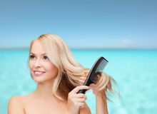 Mulher de sorriso com escova de cabelo Imagens de Stock Royalty Free