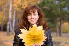 Mulher de sorriso com folhas de bordo imagens de stock
