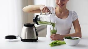 Mulher de sorriso com frasco do misturador e agitação verde filme