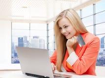 Mulher de sorriso com laptop e cartão de crédito Foto de Stock Royalty Free