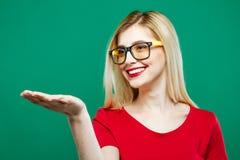 Mulher de sorriso com o cabelo louro longo, os monóculos e a parte superior vermelha guardando o espaço vazio em sua mão no fundo Imagem de Stock