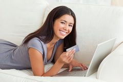 Mulher de sorriso com o cartão à disposicão que encontra-se no sofá Imagens de Stock Royalty Free