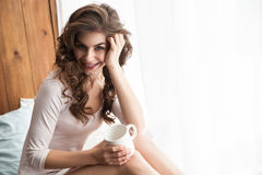 Mulher de sorriso com o copo na janela Foto de Stock