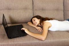 Mulher de sorriso com o portátil que olha para tomar partido em casa fotografia de stock royalty free