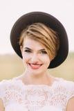 A mulher de sorriso com o profundo - os olhos verdes, o batom vermelho, os cateyes e o chapéu negro estão olhando a câmera O clos fotos de stock