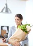 Mulher de sorriso com o telefone celular que guarda a compra Imagens de Stock