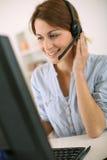 Mulher de sorriso com os auriculares que trabalham com computador Imagens de Stock Royalty Free