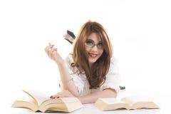 Mulher de sorriso com os livros que encontram-se no assoalho Fotos de Stock