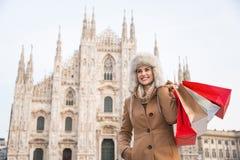 Mulher de sorriso com os sacos de compras que estão na parte dianteira do domo Fotografia de Stock Royalty Free