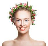 Mulher de sorriso com pele saudável e flores nos vagabundos brancos fotografia de stock royalty free
