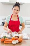 A mulher de sorriso com receita registra e vegetais na cozinha Fotografia de Stock