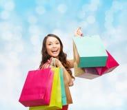 Mulher de sorriso com sacos de compras coloridos Imagem de Stock