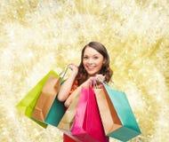 Mulher de sorriso com sacos de compras coloridos Imagem de Stock Royalty Free