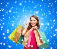 Mulher de sorriso com sacos de compras coloridos Foto de Stock