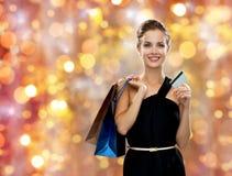 Mulher de sorriso com sacos de compras e cartão de crédito fotografia de stock