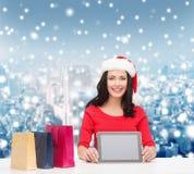Mulher de sorriso com sacos de compras e PC da tabuleta Fotografia de Stock