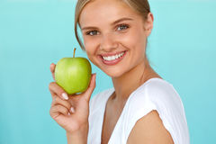 Mulher de sorriso com sorriso bonito, dentes brancos que guardam Apple Imagens de Stock