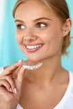 Mulher de sorriso com sorriso bonito usando os dentes que clarea a bandeja fotos de stock royalty free