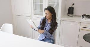 Mulher de sorriso com a tabuleta na cozinha vídeos de arquivo