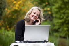 Mulher de sorriso com telemóvel e portátil Fotos de Stock