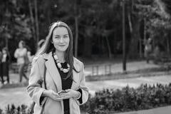 Mulher de sorriso com um sorriso perfeito, andando no revestimento no parque do outono e em olhar a câmera Fotografia de Stock Royalty Free