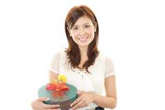 Mulher de sorriso com um presente Imagens de Stock Royalty Free