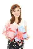 Mulher de sorriso com um presente Fotografia de Stock Royalty Free
