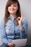 Mulher de sorriso com uma tabuleta digital foto de stock